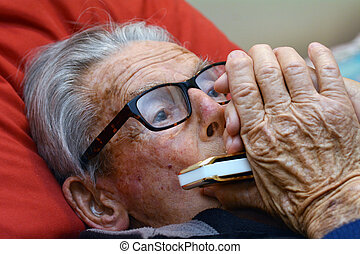 Old man play harmonica in bed. Concept photo of old age,...
