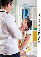 Pediatrician examining girl's lymph nodes - Asian...