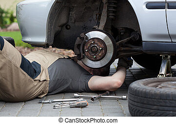 Mechanic repairing car wheel