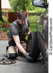Man changing car wheel - Vertical view of man changing car...