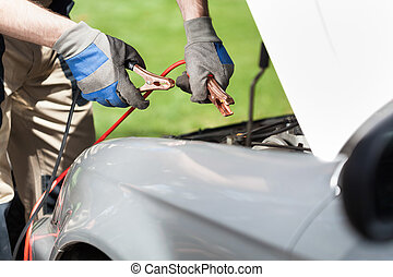 Using jumper cables to start a car battery