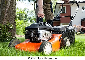 Turning on the lawn mower by gardener