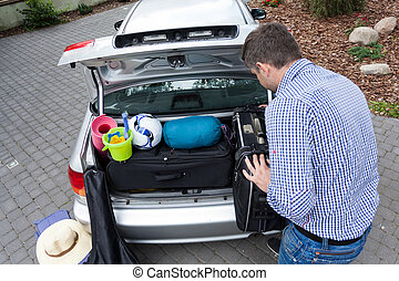 Dad preparing car trunk for holiday, horizontal