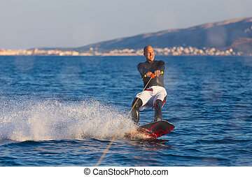 Wakeboarder in sunset. - Wakeboarder in wetsuit riding in...