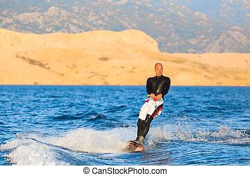 Wakeboarder in sunset - Wakeboarder in wetsuit riding in...