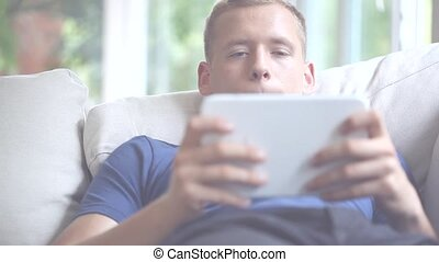 Young man spending time with tablet - Young man spending...