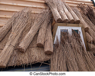 Roofing a house with traditional thatched straw roof -...