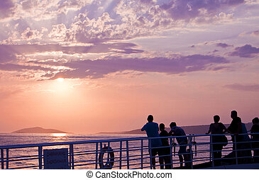 People on a ferry looking at sunset - silhouettes of people...