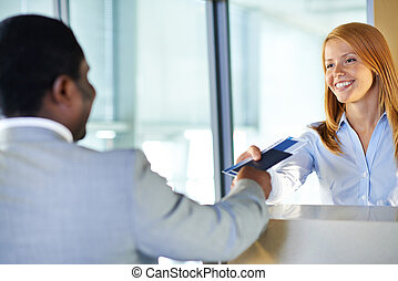 Returning documents - Attractive young woman giving passport...