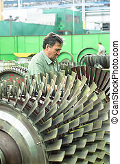 Mechanic works with part of aviation engine