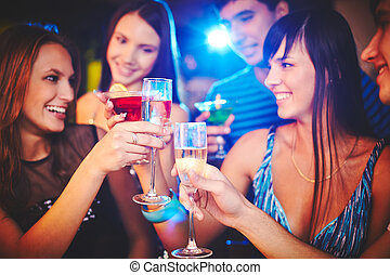 Celebrating holiday - Happy girls and guys toasting at party