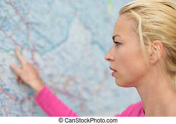 Woman pointing on map.