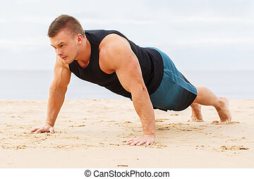 Fitness on the beach - Sport, fitness. Man doing push-up on...