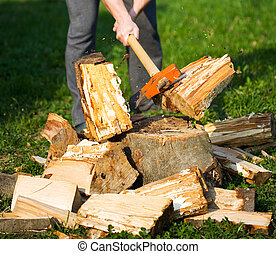 Wood splitting - Hands of a strong man splitting wood with...