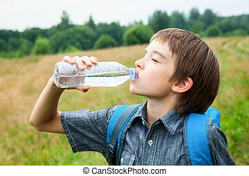 Kid drink water oudoors - Boy drinking water from pet bottle...