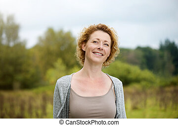 Beautiful middle aged woman smiling outdoors - Close up...