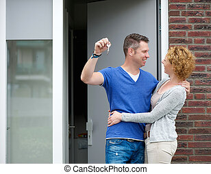 Happy couple standing outside new home with keys - Portrait...