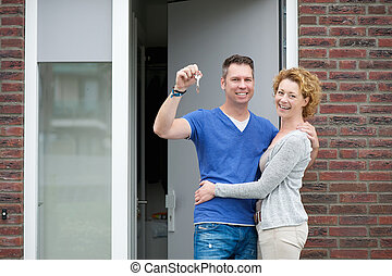 Happy couple smiling outside new home - Portrait of a happy...
