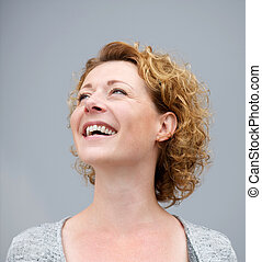 Close up portrait of a cheerful woman laughing on gray...