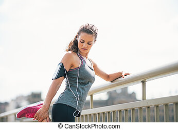 Portrait of fitness young woman stretching outdoors