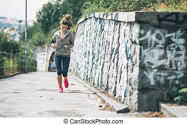 Fitness young woman jogging in the city park. rear view
