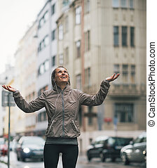 Portrait of happy fitness young woman catching rain drops in the