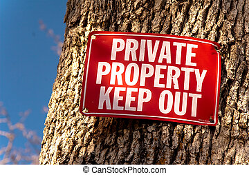 Private Property - Red Keep Out sign nailed to tree trunk, a...