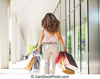 Young woman with shopping bags walking on the mall alley....