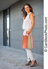 Full length portrait of happy young woman with shopping bag on t