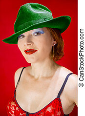 a green hat - sexy red-haired middle-aged woman dressed in a...