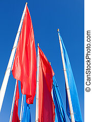 Colorful flags on blue sky background