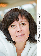 middle-aged woman brown eyes is sitting in the apartment -...
