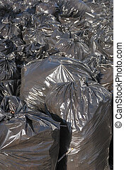 pile of black garbage bags with tons of trash, vertical -...