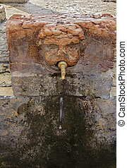 Old marble sculpture of the head with a water tap in the old...