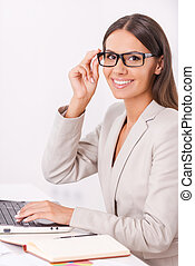 Happy businesswoman. Side view of beautiful young businesswoman holding hands clasped and smiling while sitting at her working place