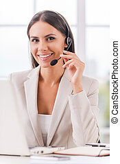 Supporting your business. Beautiful young businesswoman adjusting her headset and smiling while sitting at her working place