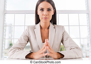 Successful businesswoman. Confident  young businesswoman holding hands clasped and looking at camera while sitting at her working place
