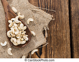 Dried Cashew Nuts on wooden background close-up shot
