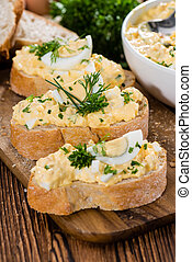 Portion of Egg Salad fresh homemade with herbs on wooden...