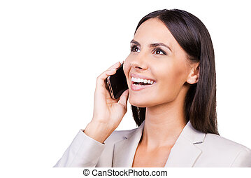 Good talk. Confident young businesswoman in suit talking on the mobile phone and smiling while standing isolated on white background