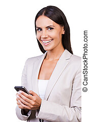 Typing business message. Confident young businesswoman in suit holding mobile phone and smiling while standing isolated on white background