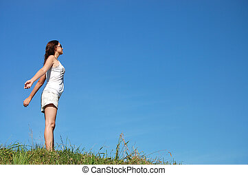 woman in field under blue sky