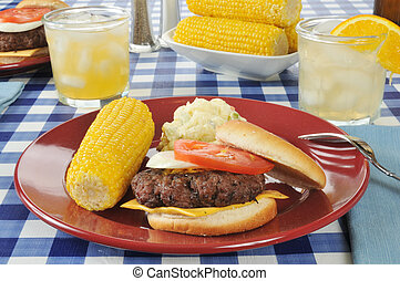 Cheeseburger with corn on the cob - A cheeseburger with...