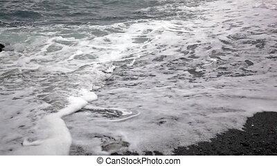 Sea waves run on the stony coast