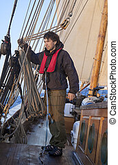 Young sailor onboard with sails behind him
