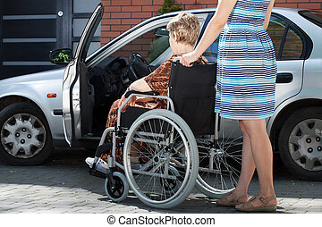 Girl helping woman on wheelchair getting into a car - Girl...