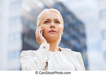 serious businesswoman with smartphone outdoors - business,...