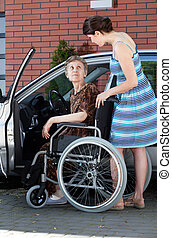 Senior female driver on wheelchair and young woman