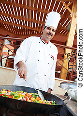 Arab chef frying meat on pan - Arab chef in cook uniform...
