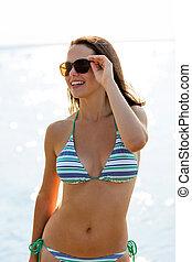 smiling teenage girl sunglasses with ball on beach - sea,...